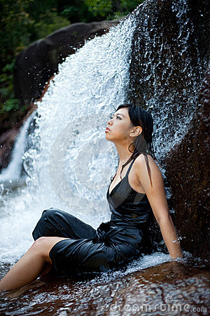 Relaxing young woman at waterfall
