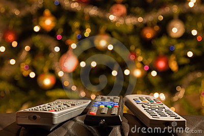 Remote controls in front of lit christmas tree