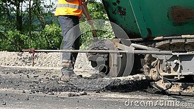 Reparation av en huvudväg, vägbyggnationer arbetaren i en orange waistcoat, en special likformig, med en skyffel lastar av stock video