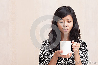 Beautiful asian girl blowing a hot beverage