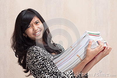 Asian student holding huge amount of books and expressing really heavy