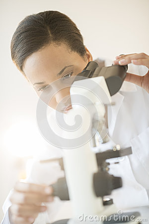 Researcher Adjusting Microscope In Laboratory