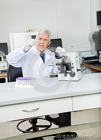 Researcher Analyzing Microscope Slide In Lab