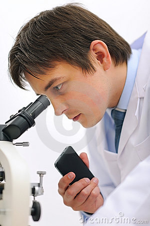 Researcher looking in microscope and making notes