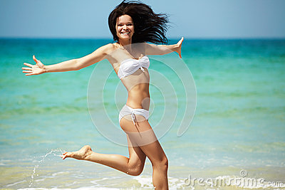 Resort, sea and health body. Young happy girl running on beach