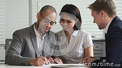 Responsabile di firma della stretta di mano del contratto di prestito bancario delle coppie miste felici di etnia stock footage
