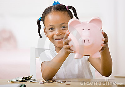 Responsible girl putting money into piggy bank