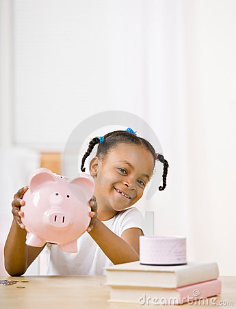 Responsible girl putting money into piggy bank