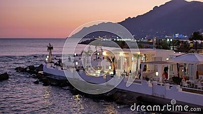Restaurante iluminado y bordeado en la orilla del mar y en las colinas almacen de metraje de vídeo