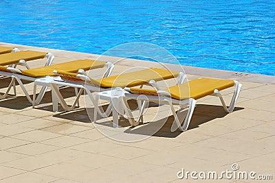 Restbeds de la piscina alrededor de una piscina