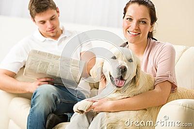 Resting joyful couple sitting and petting dog