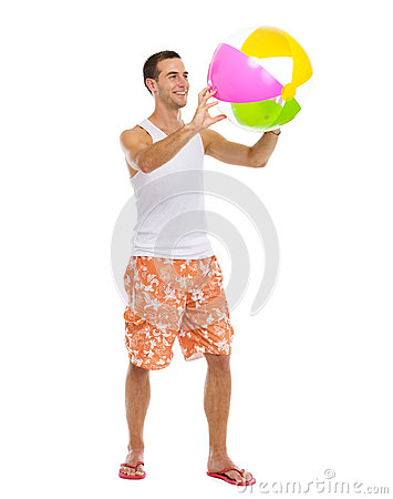 Resting on vacation man playing with beach ball