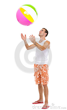 Resting on vacation man throwing beach ball up