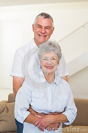 Retired couple embracing and smiling at camera