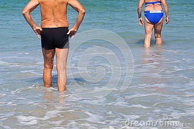 Retired couple walking in the sea