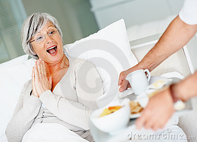 Retired female being served breakfast in bed