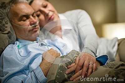 Retired ill man and caring wife sleeping