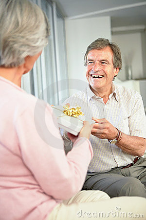 Retired man giving woman a present on birthday