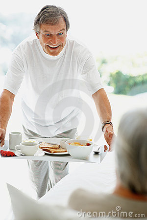 Retired man serving breakfast to the woman in bed