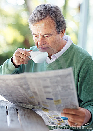 Retired old man reading newspaper in morning