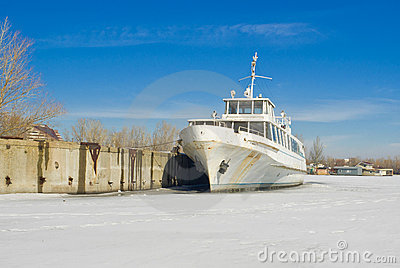 Retired pleasure boat on a winter river.