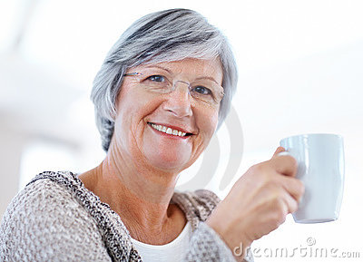 Retired smiling senior woman drinking coffee