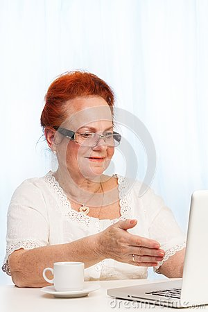 Retired woman pointing at laptop screen