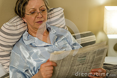 Retired woman reading newspaper before sleeping