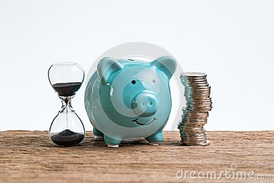 Retirement saving money piggy bank as long term investment concept with stack of coins and sandglass or hourglass on wood table Stock Photo