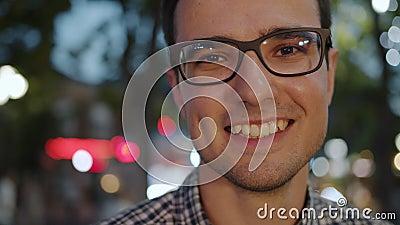 Retrato aproximado do jovem brunet feliz em óculos ao ar livre à noite video estoque