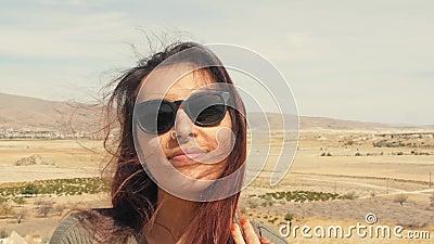 Retrato competido misturado de sorriso atrativo novo da menina em um deserto Mulher feliz do turista que levanta na câmera com o  vídeos de arquivo