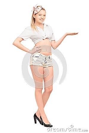Retrato completo do comprimento de uma fêmea nova em gesticular das calças curtas