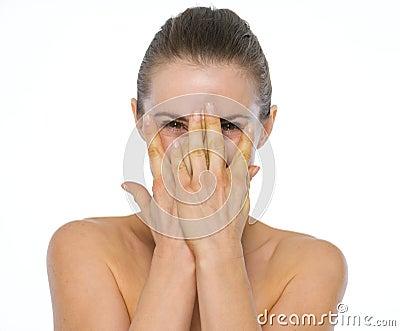 Retrato da beleza da jovem mulher que esconde atrás das mãos