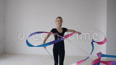 Retrato da ginástica graciosa bonito que gira a fita colorida na frente da câmera no estúdio branco gymnastics filme