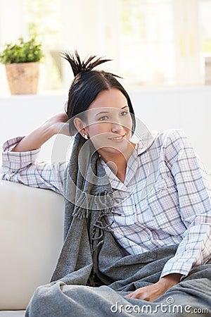Retrato da jovem mulher no pyjama que tem a cobertura