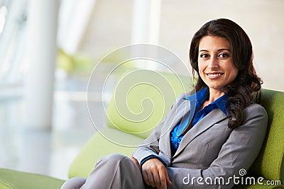 Retrato da mulher de negócios que senta-se no sofá