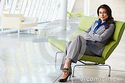 Retrato da mulher de negócios que senta-se no sofá no escritório moderno