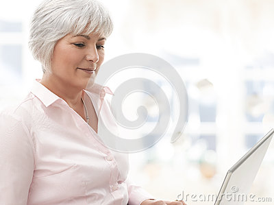 Mulher superior de sorriso que trabalha no portátil