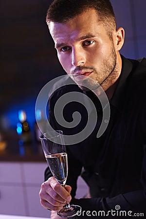 Retrato da noite do homem novo com flauta de champanhe