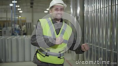 Retrato de alegre trabalhador caucasiano que trabalha com capacete protetor, dançando ao fundo de tubos de aço Feliz video estoque