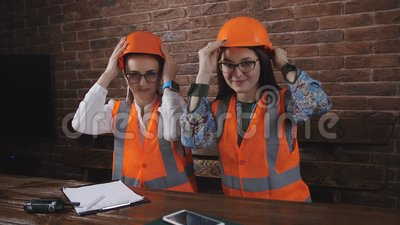 Retrato de duas mulheres nos capacetes de segurança vestindo da tabela no escritório da construção vídeos de arquivo