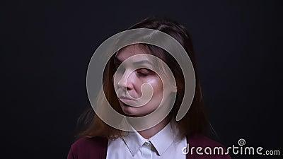 Retrato de estar cansado de bostezo de la empresaria morena joven y el ser agujereado en fondo negro metrajes