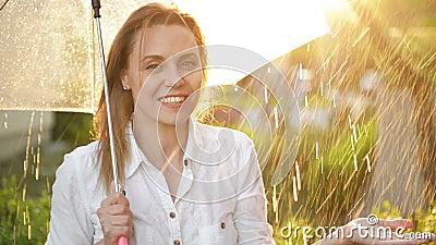 Retrato De Garota Cheerful Segurando Guarda-Chuva E Pegando Chuva Cai Com Sorriso Ela está estressando a mão e filme