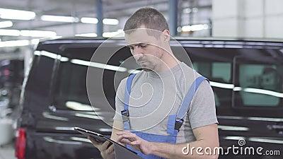 Retrato de jovem mecânico caucasiano datilografado em tablet, olhando para a câmera e mostrando o polegar para cima Homem alegre  filme