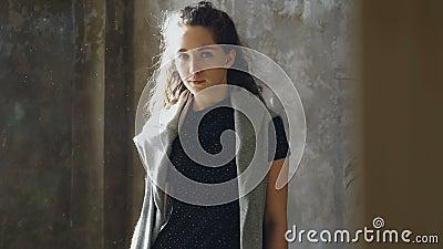 Retrato de la chica joven atractiva todavía que se coloca adentro y que mira la cámara Vuelo del polvo alrededor del sitio solead metrajes