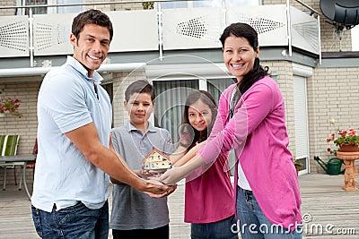 Retrato de la familia joven con un modelo de la casa