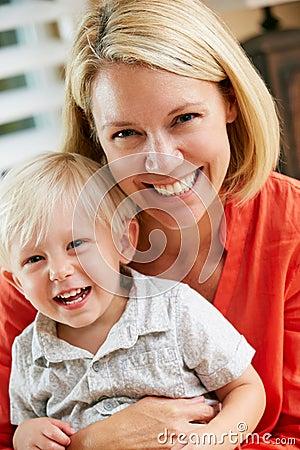 Retrato de la madre y del hijo que se sientan en el sofá en casa