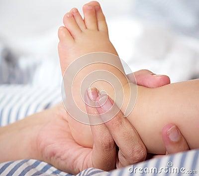 Retrato de la mano femenina que lleva a cabo el pie del bebé