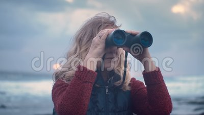 Retrato de la mujer madura con los prismáticos en un fondo de la tormenta contra un fondo dramático del cielo almacen de metraje de vídeo