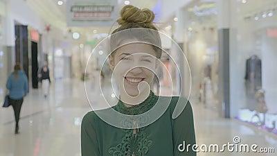 Retrato de levantar de riso do blogger fêmea novo da forma e de olhar a câmera na alameda antes de sua sessão da compra - vídeos de arquivo